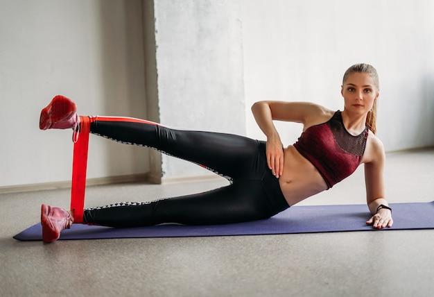 Modello attraente della ragazza di forma fisica di usura di sport della giovane donna in forma attraente che fa stretching con la fascia elastica alla classe di allenamento in studio loft