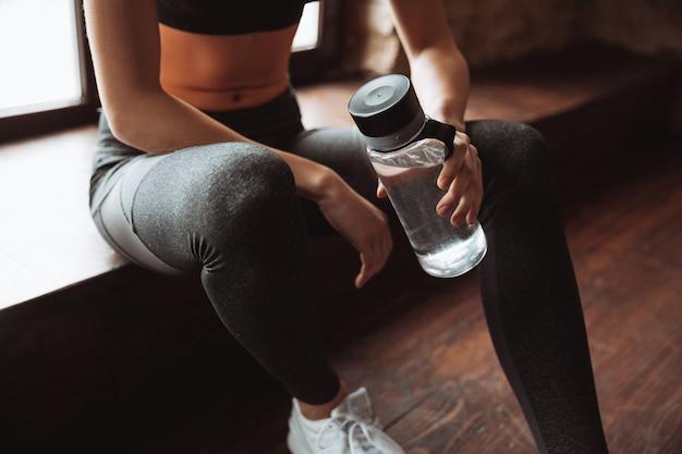 Donna attraente di forma fisica che si siede in ginnastica e che tiene acqua.