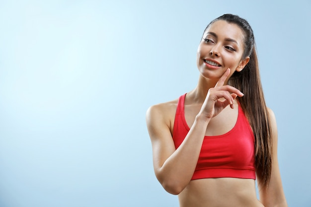 Attraente donna fitness pensando sul muro grigio