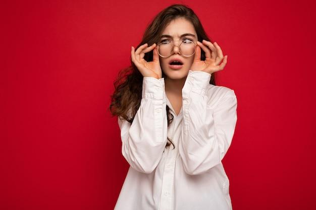 Attraente divertente positivo scioccato stupito sorpreso giovane donna bruna riccia che indossa una camicia bianca