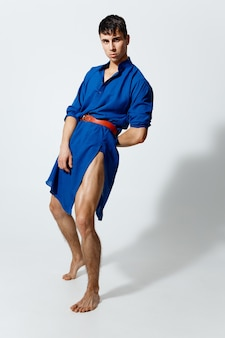 Ragazzo gay attraente in un vestito blu su uno sfondo chiaro che balla in piena crescita