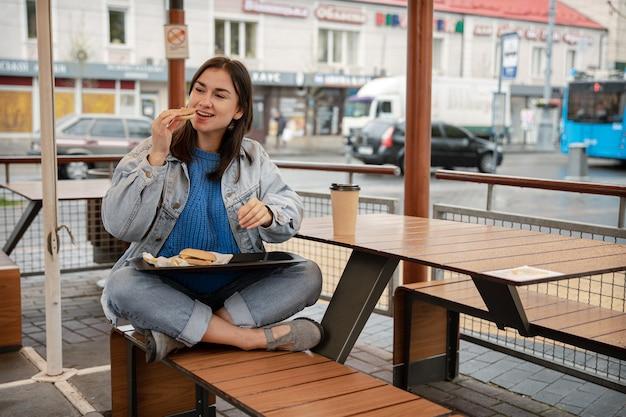 Ragazza attraente in stile casual mangia un hamburger con caffè seduto sulla terrazza estiva di un caffè.