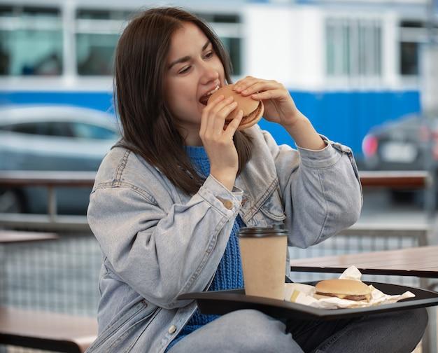 Ragazza attraente in stile casual mangia un hamburger con caffè seduto sulla terrazza estiva.
