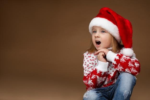 Attraente ragazza in abbigliamento accogliente e cappello di natale si siede sul pavimento e canta una canzone di natale, immagine isolata su sfondo marrone