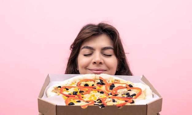 Ragazza attraente che si gode l'odore della pizza appena sfornata su uno sfondo rosa.