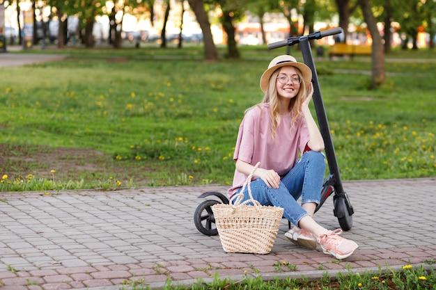 Ragazza attraente in un cappello con uno scooter elettrico nel parco per una passeggiata in estate