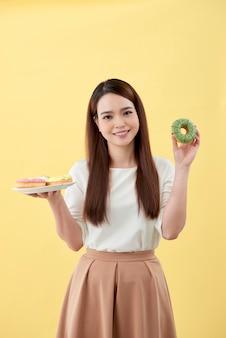 Ragazza attraente che tiene ciambelle fresche e si diverte con roba dolce. buon umore, concetto di dieta.