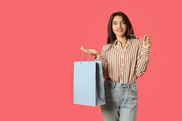 La ragazza attraente tiene il sacco di carta blu su fondo rosa.