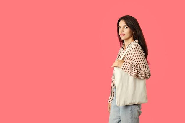 La ragazza attraente tiene la borsa di cotone su sfondo rosa, spazio per il testo.