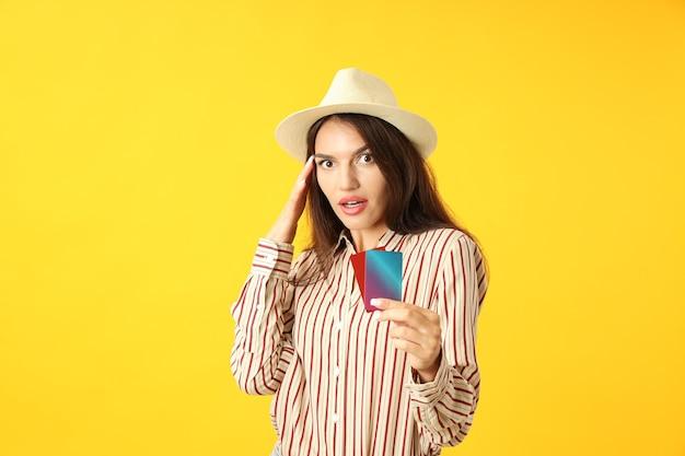 La ragazza attraente tiene le carte di credito su fondo giallo.