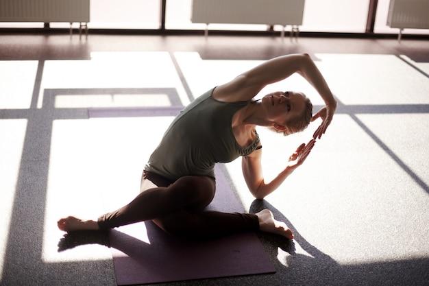 Una ragazza attraente è seduta a gambe incrociate, chinandosi, eseguendo un'asana yoga. la ragazza è impegnata nello yoga in uno studio moderno