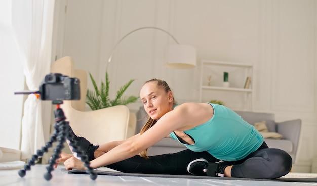 Una ragazza attraente sta vlogging sul fitness online, sta filmando un vlogging facendo esercizi di stretching su un tappeto in una stanza luminosa. una giovane ragazza sta studiando a distanza online mentre scrive su un blog.