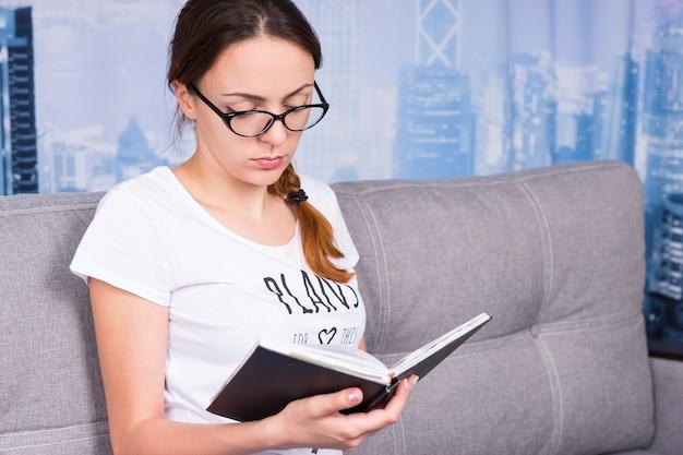 Attraente ragazza che legge un libro e indossa gli occhiali seduta su un divano nel soggiorno in un'atmosfera rilassata