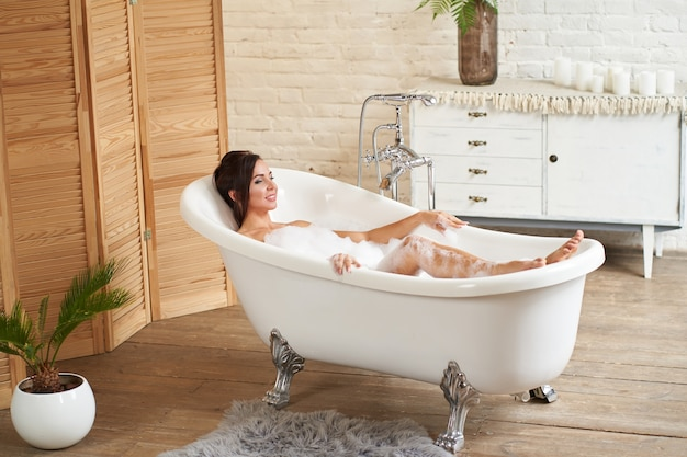 Ragazza attraente si rilassa in bagno e riposa sullo sfondo di un bellissimo interno luminoso