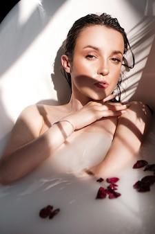 Una ragazza attraente che si distende nella vasca da bagno con petali su sfondo chiaro - ritratto di moda