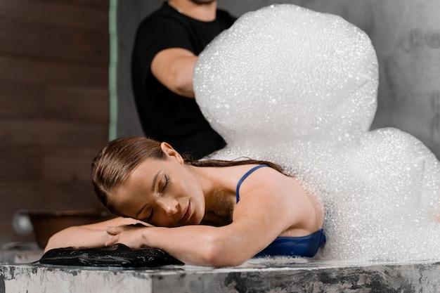 Ragazza attraente che si rilassa nella stazione termale. il massaggiatore sta facendo il peeling con la schiuma nell'hammam della spa turca.