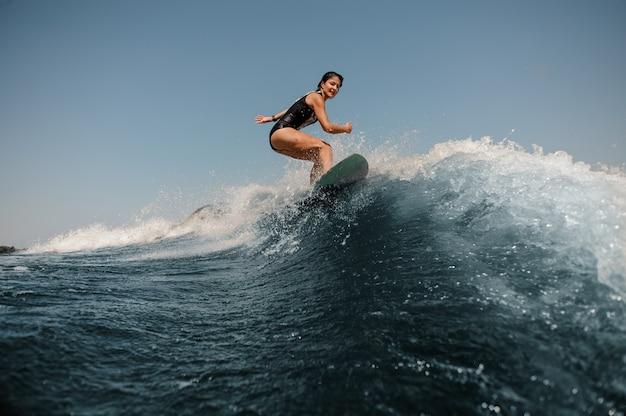 Ragazza attraente che guida sul wakeboard sul lago libero