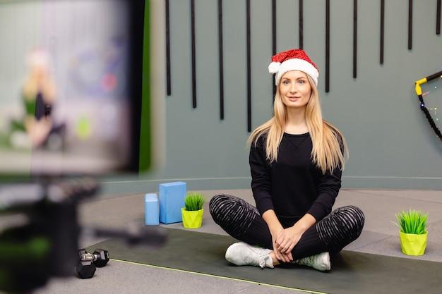 Ragazza attraente in cappello della santa sta facendo esercizi di fitness e si registra sulla fotocamera.