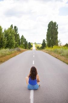Attraente ragazza seduta sull'asfalto e posa in mezzo alla strada asfaltata vicino al campo