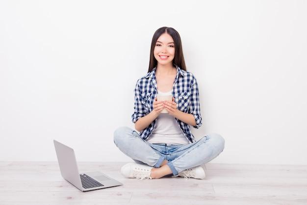 Attraente ragazza seduta sul pavimento tenendo la tazza di tè