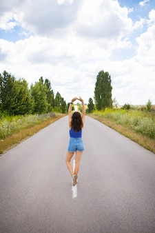 Ragazza attraente, sta in posa, alza le mani nel mezzo di una strada asfaltata vicino al campo