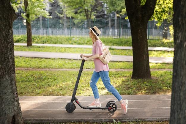 Attraente ragazza con cappello di paglia con scooter nel parco durante una passeggiata estiva