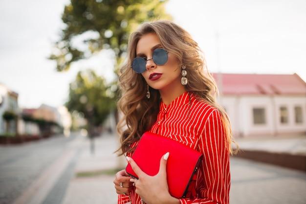 Ragazza attraente in occhiali da sole, camicia a strisce rossa che tiene borsa rossa.