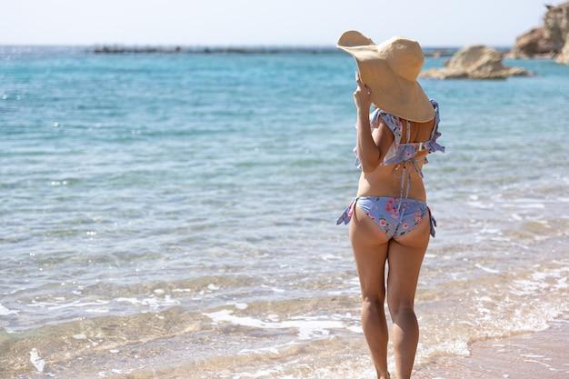 Una ragazza attraente in costume da bagno e un grande cappello si trova in riva al mare.