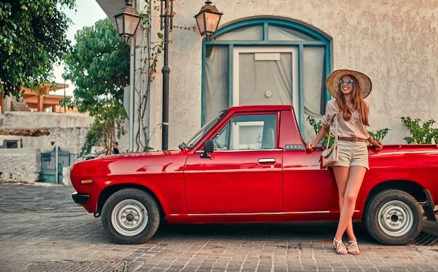 Turista della ragazza attraente in una camicetta, occhiali da sole e un cappello di paglia si trova vicino a un'auto rossa. il concetto di turismo, viaggi, tempo libero.