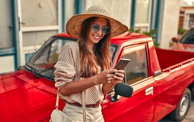 Turista della ragazza attraente in una camicetta, occhiali da sole e un cappello di paglia si trova vicino a un'auto rossa e utilizza lo smartphone. il concetto di turismo, viaggi, tempo libero.