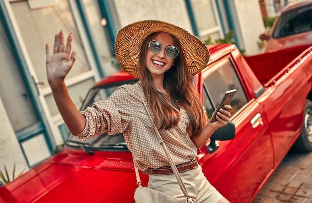 Turista della ragazza attraente in una camicetta, occhiali da sole e un cappello di paglia si trova vicino a una macchina rossa, utilizzando smartphone e saluta qualcuno. il concetto di turismo, viaggi, tempo libero.