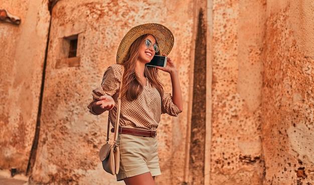 Turista attraente della ragazza in una camicetta, occhiali da sole e un cappello di paglia che parla al telefono da un antico edificio della città. il concetto di turismo, viaggi, tempo libero.