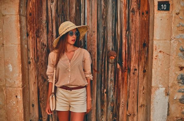 Turista della ragazza attraente in occhiali da sole, una camicetta e un cappello di paglia da porte in legno di un edificio. il concetto di turismo, viaggi, tempo libero.