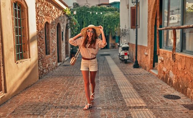 Attraente ragazza turistica in occhiali da sole, una camicetta e un cappello di paglia sta camminando lungo i vicoli della città. il concetto di turismo, viaggi, tempo libero.