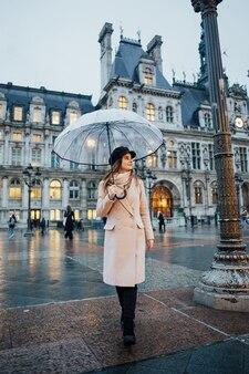 Attraente ragazza viaggiatore con ombrello trasparente gode della vista