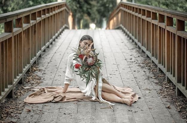 Una ragazza attraente in abito bianco si siede sul ponte con un mazzo di fiori esotici.