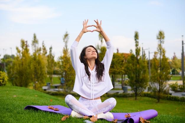 Una ragazza attraente in abiti sportivi bianchi fa mudra yoga con le mani alzate, seduta su un tappetino al parco cittadino, allenamento all'aperto