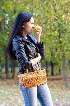 Ragazza attraente con un cesto di frutta appena colta in piedi all'aperto sotto il sole mangiando una mela