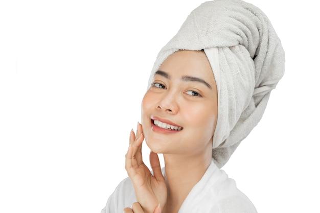 Ragazza attraente con l'asciugamano da bagno sulla testa che sorride con la mano che tiene il mento