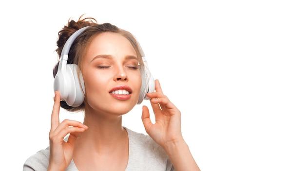 Attraente ragazza con gli occhi chiusi che ascolta la musica tramite le cuffie su sfondo bianco suono gro...