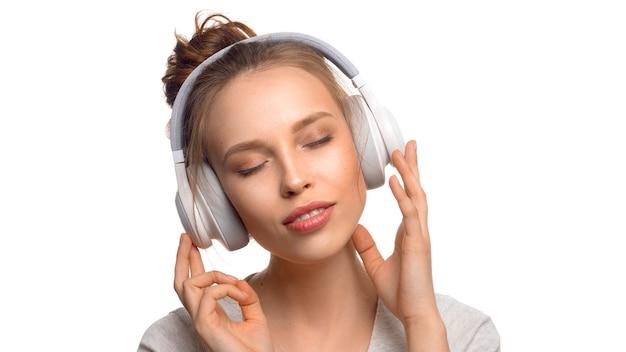 Ragazza attraente con gli occhi chiusi che ascolta la musica tramite le cuffie su fondo bianco