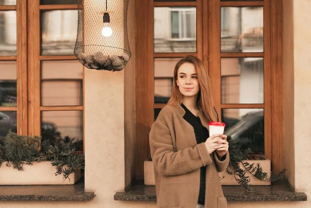 Ragazza attraente con una tazza di caffè in mano, indossa un cappotto beige, in piedi contro il muro con finestre e guardando al lato
