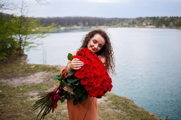 Attraente ragazza con i capelli ricci e un sorriso sul viso con un enorme mazzo di rose rosse su uno sfondo di lago blu. calda giornata estiva, giovane donna felice, emozioni di gioia