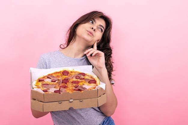 Ragazza attraente con pizza in una scatola per la consegna su uno sfondo rosa.