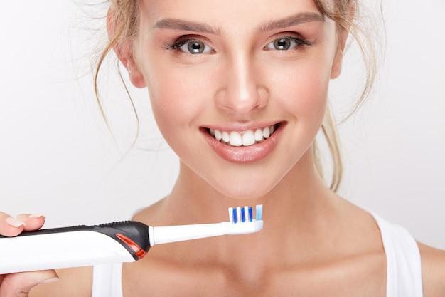 Ragazza attraente con denti bianchi come la neve su sfondo bianco studio, concetto di odontoiatria, sorriso perfetto, tenendo lo spazzolino da denti elettrico, primi piani.