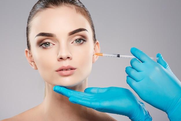 Ragazza attraente con le sopracciglia folte al fondo dello studio, le mani del medico che indossano guanti blu vicino al viso del paziente, tenendo la siringa con botex vicino al viso, concetto di bellezza.