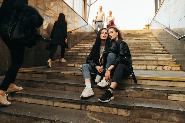Amiche attraenti sono sedute sulle scale all'uscita della metropolitana con una bottiglia di vino