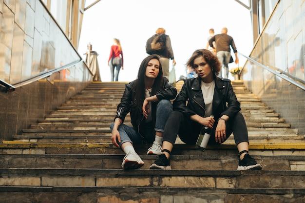 Amiche attraenti sono sedute sulle scale