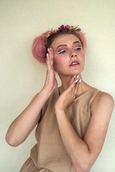 Donna attraente e affascinante in abiti beige contro il muro con trucco alla moda