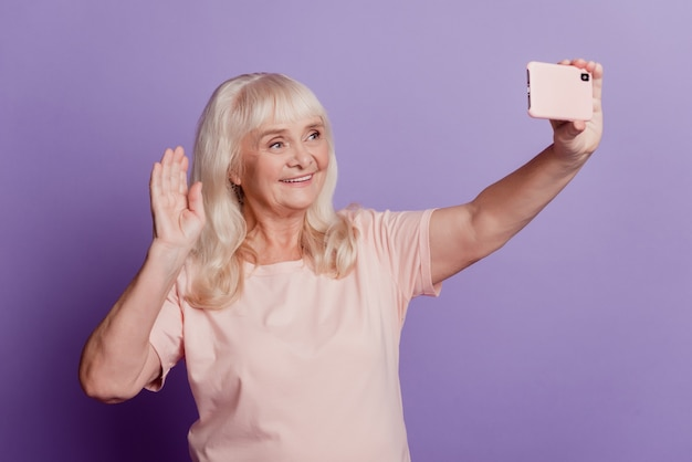 Attraente donna anziana dai capelli grigi che fa selfie isolato su sfondo viola